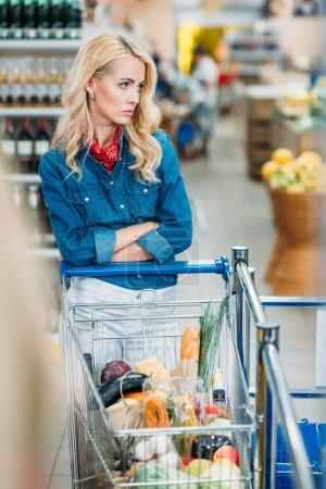 Photo pour Portrait de femme coûteuse avec chariot d'achat attendant quelqu'un dans un supermarché - image libre de droit