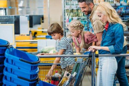 Photo pour Vue latérale de la jeune famille avec panier plein d'achats au supermarché - image libre de droit