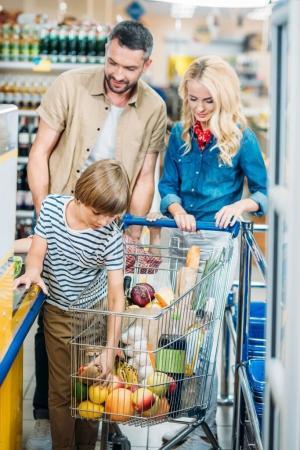 Photo pour Famille avec panier d'achat en attente au point de la trésorerie dans le supermarché - image libre de droit