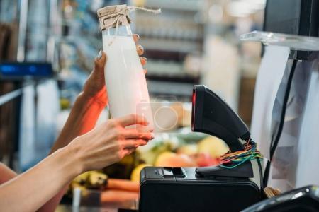 seller holding bottle of milk