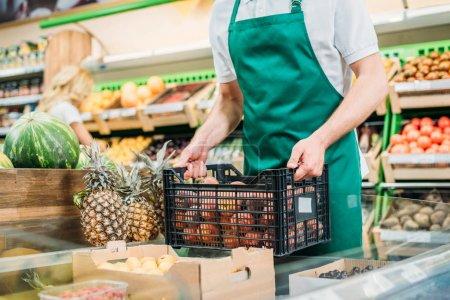 Photo pour Vue partielle de la vendeuse maintenant le panier à fruits en épicerie - image libre de droit