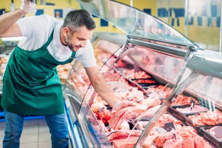 shop assistant assorting raw meat