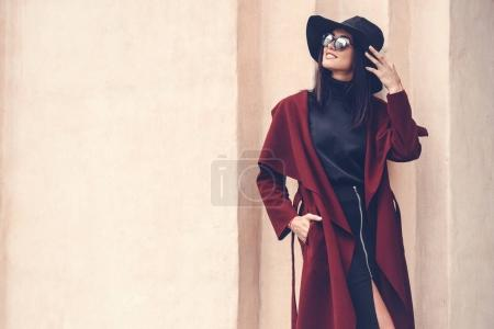 Young woman in stylish clothing posing next to old...