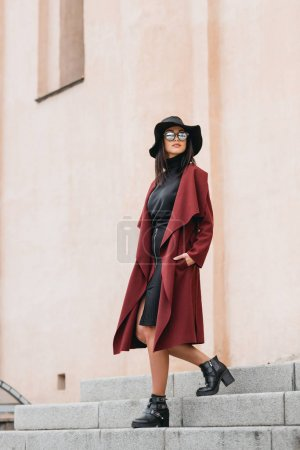 Photo for Young woman in stylish clothing walking downstairs next to old building - Royalty Free Image