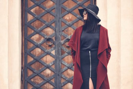 Photo for Fashionable young woman in stylish clothing posing next to old building doors - Royalty Free Image