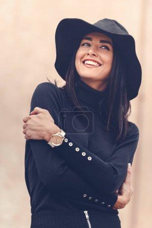 Photo pour Belle femme en vêtements noirs avec chapeau posant à l'extérieur - image libre de droit