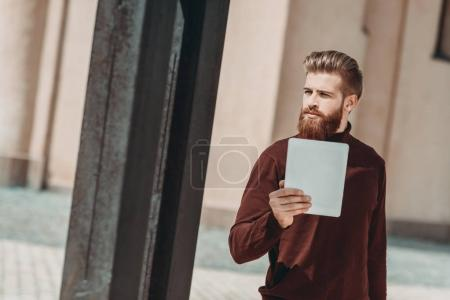 man with digital tablet outdoors
