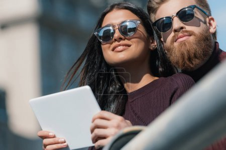 young couple with tablet outdoors