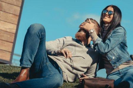 woman covering eyes of boyfriend
