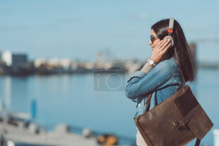 Photo for Young woman listening music with headphones outdoors at riverside - Royalty Free Image