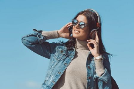 Photo for Beautiful woman listening music with headphones outdoors on sunny day - Royalty Free Image
