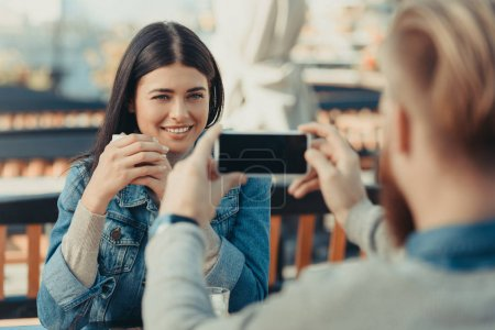 Photo for Man taking photo of happy girlfriend in cafe outdoors with smartphone - Royalty Free Image