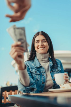 Photo for Young woman outstretching bunch of dollars in hand to waiter in cafe - Royalty Free Image