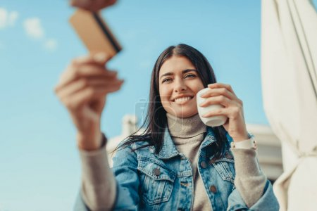 Photo for Happy woman paying with credit card in cafe outdoors - Royalty Free Image