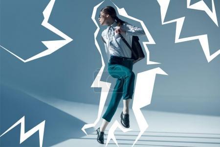 Foto de Mujer joven con estilo hipster en camisa blanca, pantalón verde y gafas mirando lejos saltando - Imagen libre de derechos