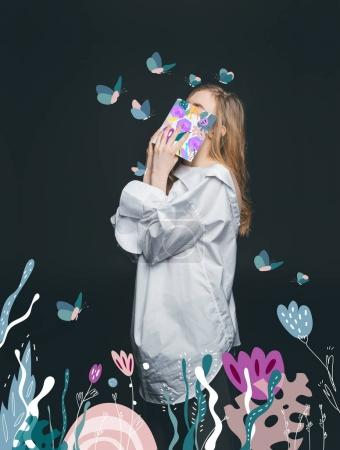 Photo for Cute blonde fashion girl hiding face by book, standing with drawn flowers and flying butterflies - Royalty Free Image