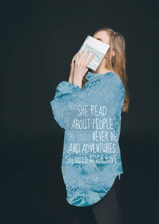 Photo for Cute blonde fashion girl hiding face by book, wearing blue shirt with text - Royalty Free Image