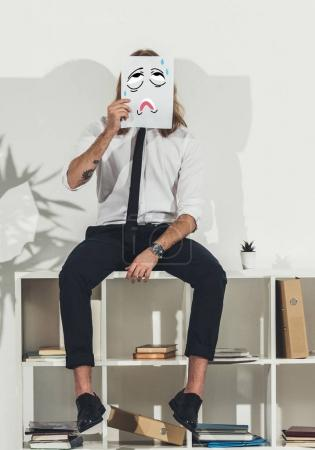 businessman holding card with funny face
