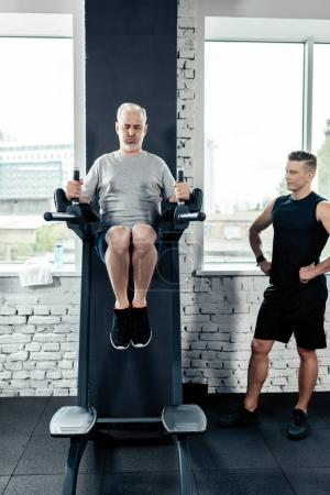 Photo for Senior sportsman doing abs on sport equipment with trainer in gym - Royalty Free Image