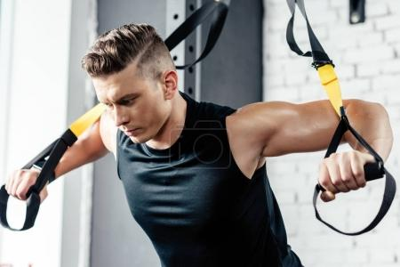 Photo for Young muscular sportsman training with trx resistance bands in gym - Royalty Free Image