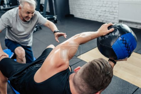 Photo pour Jeune sportif avec médecine-ball au centre sportif de formation avec formateur senior - image libre de droit
