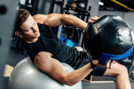 Photo for Young muscular sportsman training on fitness ball with medicine ball in gym - Royalty Free Image