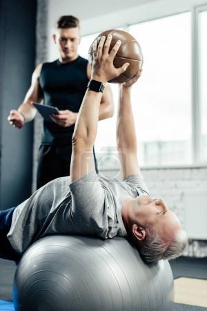senior sportsman training with medicine ball