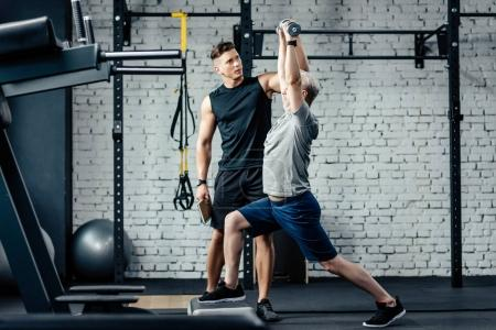 sportsman doing lunges with trainer