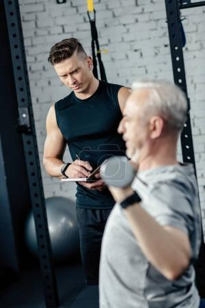 trainer looking at senior sportsman training with dumbbells in gym