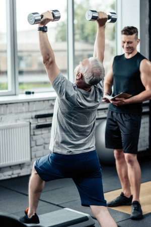 Sportsman doing lunges with dumbbells