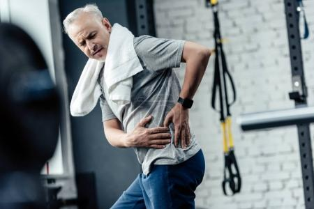 Photo for Senior sportsman with back pain after training in sport center - Royalty Free Image