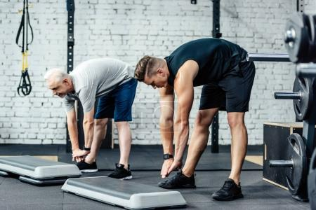 Sportsman stretching with trainer