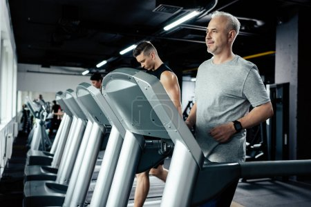Photo for Senior and young sportsmen running on treadmills in sport center - Royalty Free Image