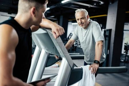 Photo for Senior sportsman running on treadmill with trainer in gym - Royalty Free Image