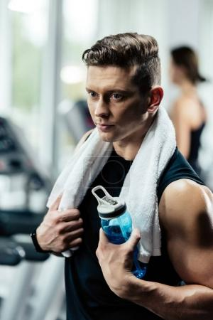 Photo for Young sportsman resting after training with sport bottle and towel in gym - Royalty Free Image