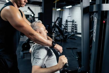 Photo for Senior sportsman lifting weights with young trainer in gym - Royalty Free Image