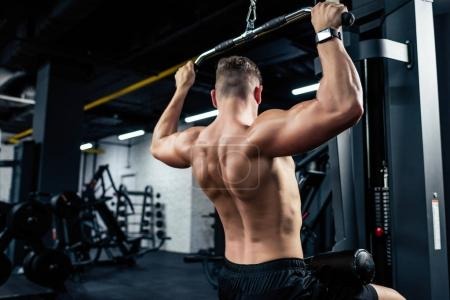 Photo for Young muscular shirtless sportsman lifting weights in sport center - Royalty Free Image