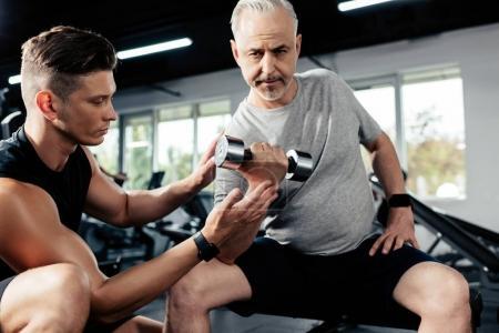 senior sportsman with dumbbell