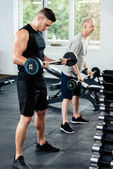 sportsmen training with barbells