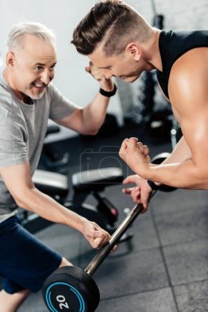 Photo pour Entraînement sportif senior excité avec haltère et jeune entraîneur en salle de gym - image libre de droit