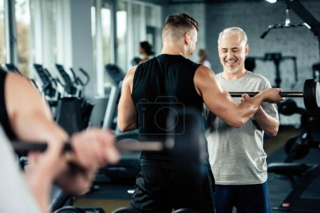Photo for Senior sportsman training with barbell and young trainer in gym - Royalty Free Image