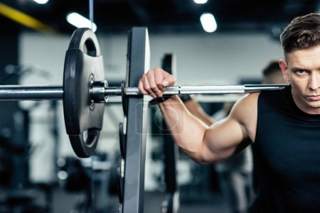 Photo for Young muscular sportsman lifting barbell in sport center - Royalty Free Image