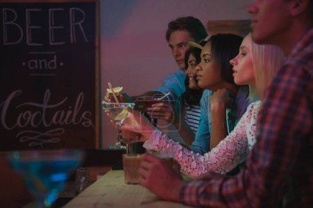 Foto de Grupo multiétnico de amigos bebiendo cócteles de alcohol juntos en contador en la barra - Imagen libre de derechos
