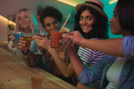 Foto de Enfoque selectivo de amigos multiculturales con cócteles teniendo fiesta juntos en el bar - Imagen libre de derechos