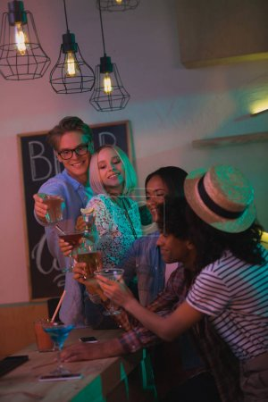 Photo pour Multiethniques amis avec des boissons d'alcool ayant parti en bar - image libre de droit