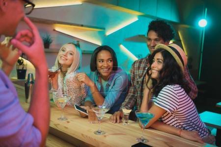 Foto de Sonrientes amigos multiculturales con bebidas pasando tiempo juntos en la barra - Imagen libre de derechos