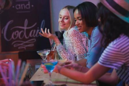 Photo pour Vue latérale de jeunes femmes multiculturelles faisant la fête ensemble dans un bar - image libre de droit