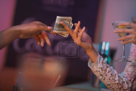 Woman paying barman for cocktails