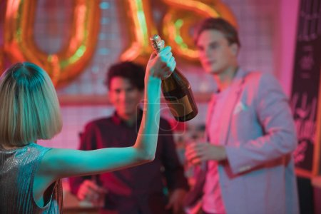 Photo for Selective focus of woman with bottle of champagne in hand with friends having party in bar - Royalty Free Image