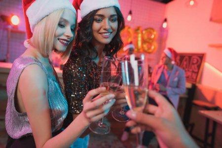 Photo pour Vue partielle du sourire des amis tinter les verres de champagne tout en ayant la fête du nouvel an - image libre de droit
